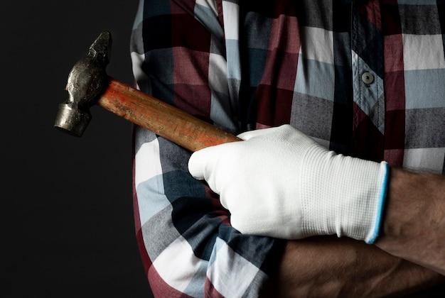 Réparateur main dans la construction de gants agrandi avec outil marteau.