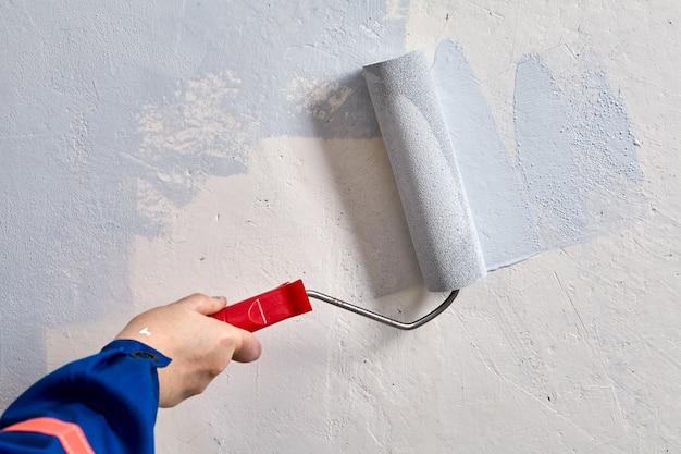 Le réparateur peint le mur à l'aide d'un rouleau à peinture pendant la rénovation.
