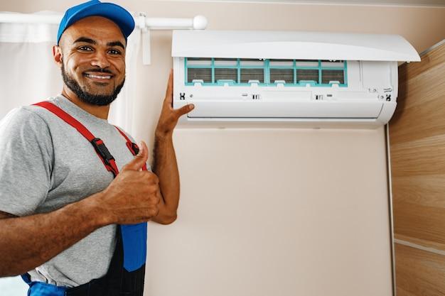 Réparateur professionnel installant un climatiseur dans une pièce
