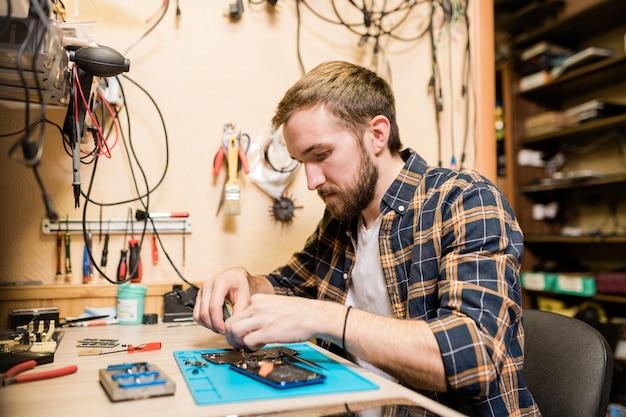 Réparateur professionnel se penchant sur un smartphone cassé et réparant de petits détails tout en travaillant par table en atelier