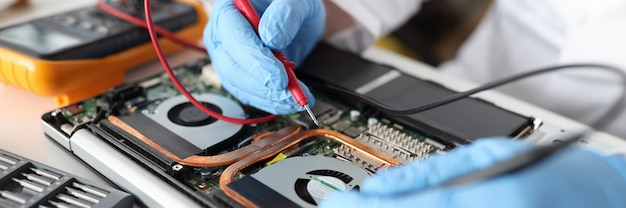 Réparateur professionnel tenant un testeur rouge dans des gants en caoutchouc sur gros plan d'ordinateur portable. réparation du concept d'équipement électronique