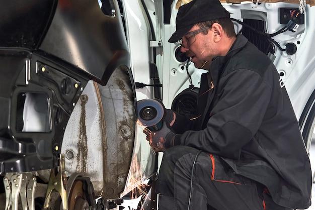 Un réparateur réparera une voiture endommagée. travailler avec une meuleuse d'angle pour fixer le corps métallique.
