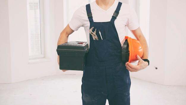 Le réparateur tenant la boîte à outils dans la pièce en cours de rénovation
