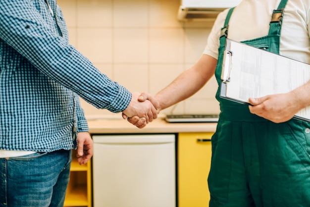 Réparateur en uniforme et client se serrent la main, bricoleur.