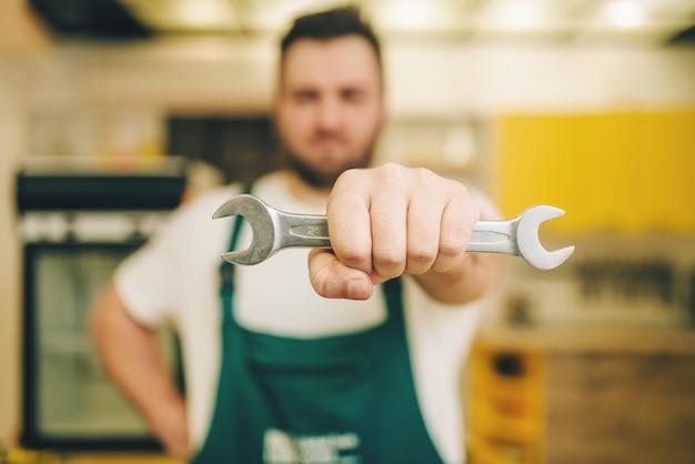 Réparateur en uniforme détient une clé, bricoleur