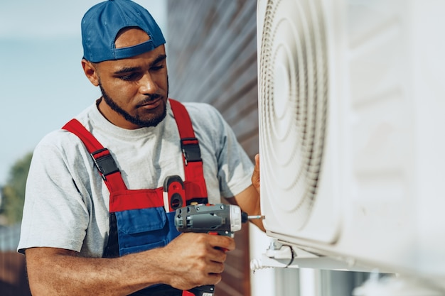 Réparateur en uniforme installant l'unité extérieure du climatiseur
