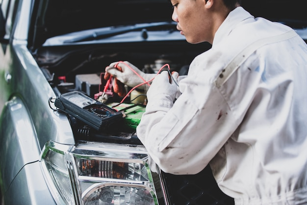 Réparateur de voiture vêtu d'un uniforme blanc debout et tenant une clé qui est un outil essentiel pour un mécanicien