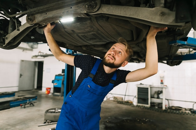 Réparateurs inspectant le fond de la voiture