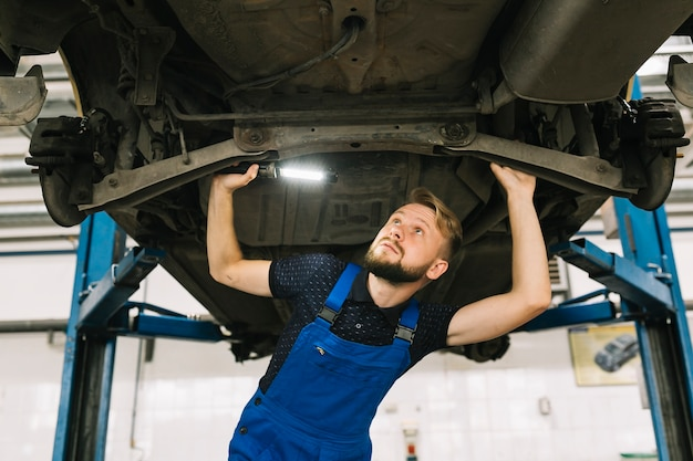 Réparateurs inspectant la transmission du véhicule