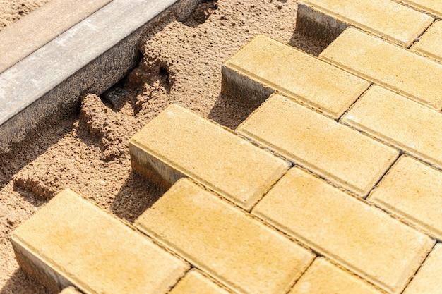 Réparation de la chaussée et pose de dalles de pavage sur la passerelle, cubes de tuiles empilés sur l'arrière-plan. pose de dalles dans la zone piétonne de la ville, remplissage de sable. tuiles et bordures de route.
