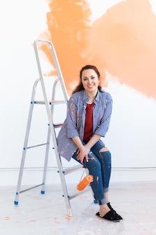 Réparation dans l'appartement. heureuse femme peint le mur avec de la peinture.