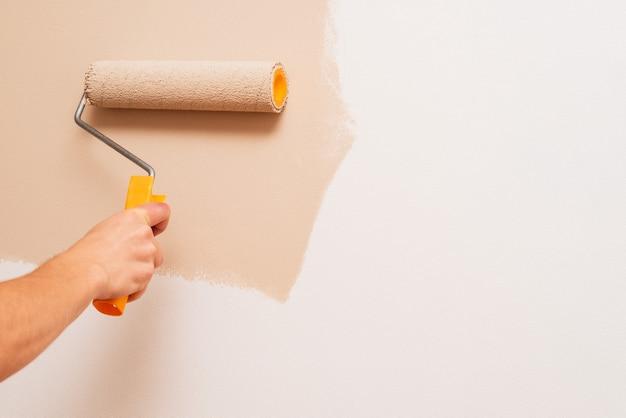 Réparation dans la maison. un homme peint les murs avec un rouleau en beige. concept avec espace de copie pour le texte