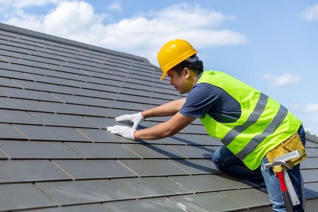 Réparation du toit, travailleur avec des gants blancs remplaçant les carreaux gris ou les bardeaux sur la maison avec du bleu