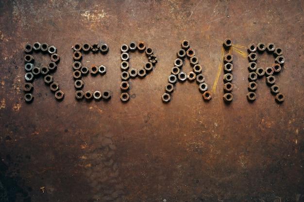 Réparation de mot faite d'écrous de vis sur une surface métallique rouillée