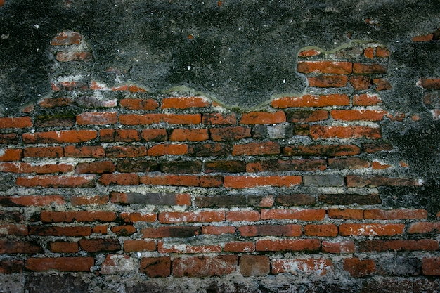 Réparation de mur de briques rouges anciennes par du ciment, fond de texture mur brique fissure