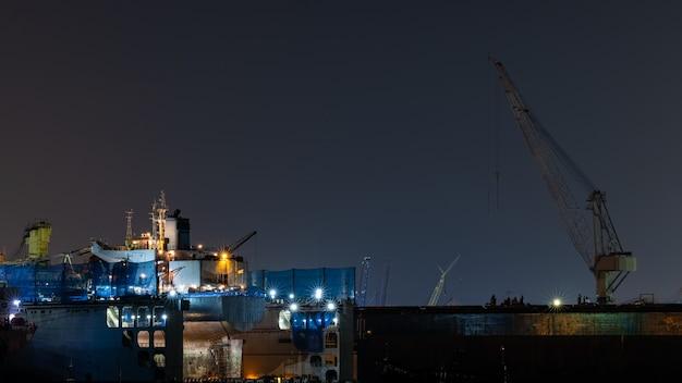 Réparation de navires pétroliers conteneurs au chantier naval la nuit. peut être utilisé pour le concept d'expédition ou de transport.