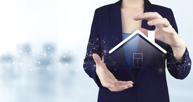 Réparation et rénovation, services d'entretien. deux mains tenant une icône holographique virtuelle smart home avec un arrière-plan flou clair. système de contrôle domotique intelligent.