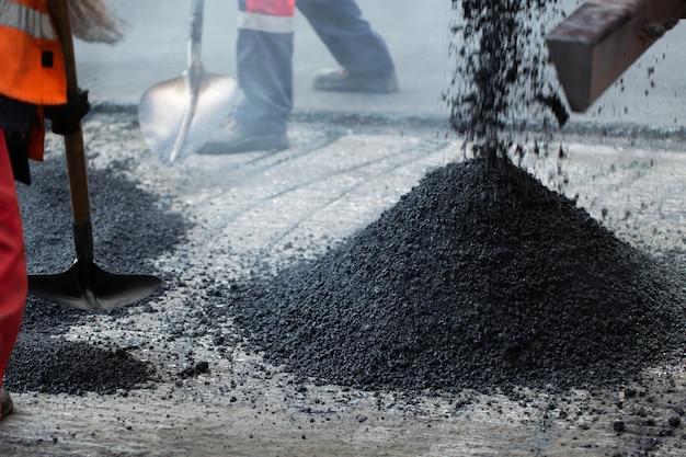 Réparation des routes, autoroutes et trottoirs. patcher. travailler avec une pelle s'endort dans la fosse.