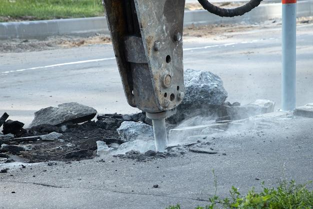 Réparation de routes. enlèvement d'une ancienne couche d'asphalte avec un marteau hydraulique. reconstruction de la chaussée.