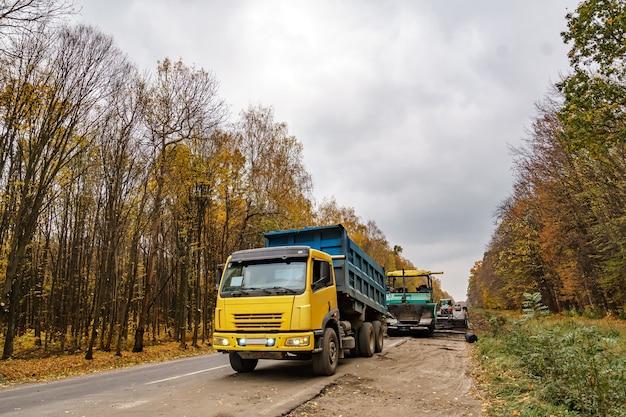 Réparation de routes. pose de l'asphalte neuf. machines spéciales lourdes. camion en opération. vue de côté. fermer.