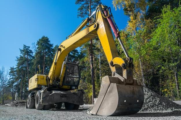 Réparation de routes, pose d'asphalte. pelle sur pneus jaune