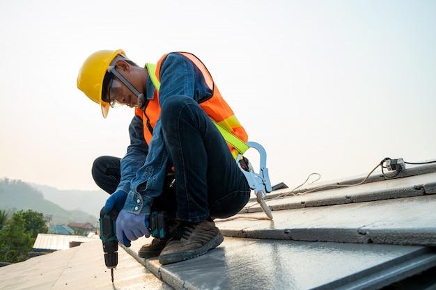 Réparation de toit, travailleur de la construction à l'aide d'un pistolet à clous pour installer un nouveau toit sur le toit supérieur, bâtiment résidentiel en construction concept