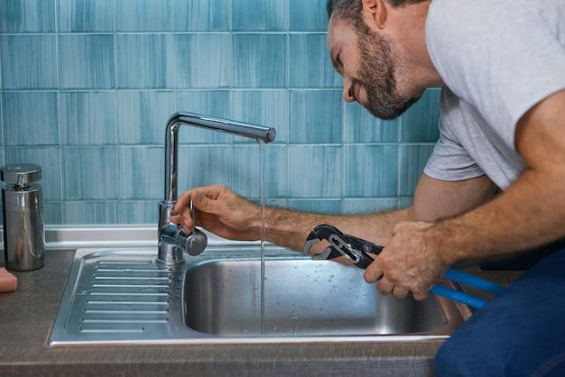 Réparer une fuite en gros plan d'un réparateur professionnel à l'aide d'une clé à pipe tout en examinant et en réparant