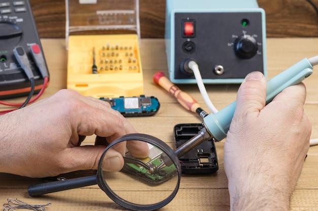 Réparez un téléphone portable à la loupe.