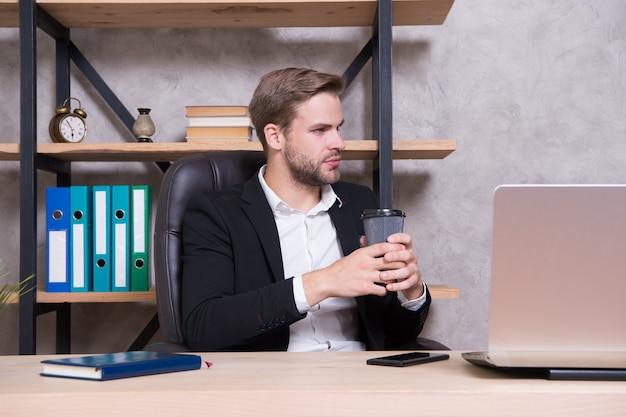 Repas d'affaires. homme d'affaires buvant du café. un homme confiant utilise un ordinateur portable. lieu de travail du patron. bel homme au bureau d'affaires. inspiré d'une tasse de café frais. concept de siège social de pdg. décision commerciale.