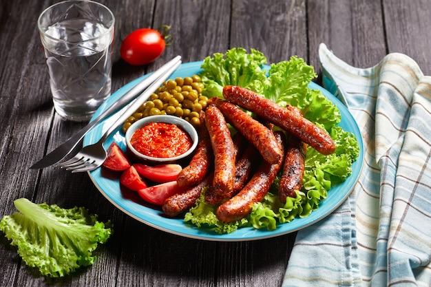 Repas anglais : saucisses de porc chipolata rôties et servies sur une assiette bleue avec du ketchup aux tomates, des tomates, de la laitue verte et des pois sur une surface en bois rustique, vue de dessus, gros plan