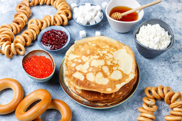 Repas du festival de maslenitsa. blini aux crêpes russes avec confiture de framboises, miel, crème fraîche et caviar rouge, morceaux de sucre, fromage cottage à la lumière