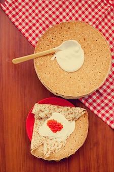 Repas du festival de la maslenitsa de mardi gras. blini aux crêpes russes avec de la crème fraîche et du caviar rouge sur un mur en bois
