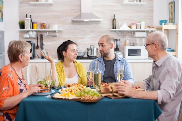 Repas de famille multi-génération autour de la table dans la cuisine. man holding verre à vin. pommes de terre assaisonnées savoureuses.