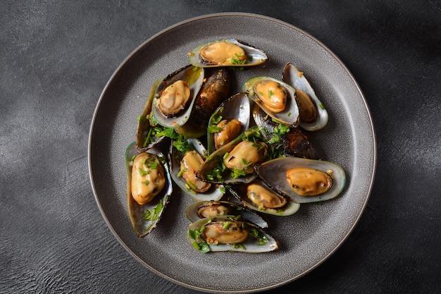 Repas français classique moules marinière moules marinara avec ail, sauce, citron et persil.