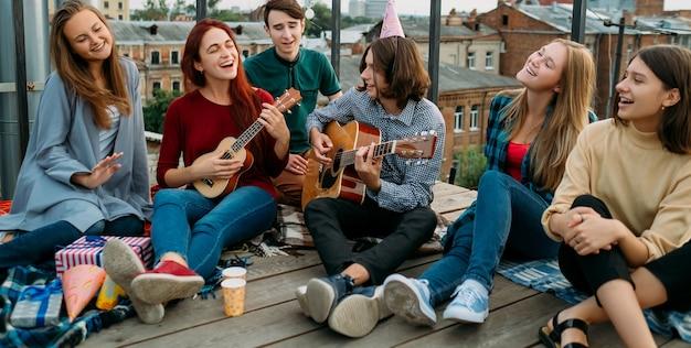 Repas de groupe d'amis. chanter sur une guitare. mode de vie des esprits libres. loisirs adolescents hipster urbain