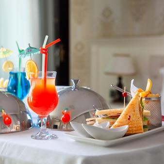 Repas d'hôtel sur une table avec sandwich, hamburger, cocktails et autres en vue latérale de la chambre