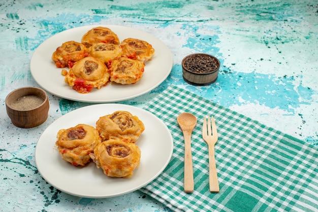 Repas de pâte cuite avec de la viande hachée à l'intérieur des assiettes sur bleu vif, pâte alimentaire repas calorie