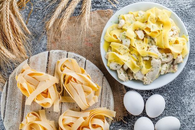 Repas de pâtes aux œufs, céréales, pâtes crues, planche de bois dans une assiette