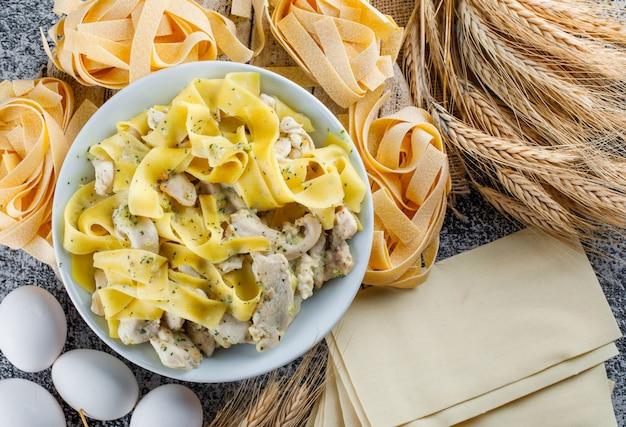 Repas de pâtes dans une assiette avec des œufs, des céréales, des pâtes crues, de la pâte