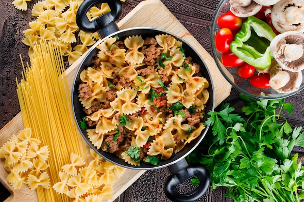 Repas de pâtes dans une poêle avec des pâtes crues, des champignons, du poivre, du persil, de la tomate