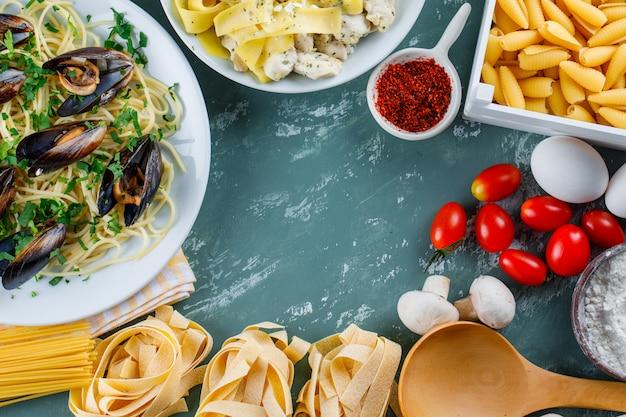 Repas de pâtes avec des pâtes crues, tomate, farine, champignon, oeufs, épices, cuillère en assiettes