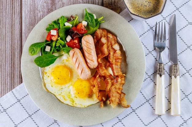 Repas pour oeuf de petit déjeuner, saucisse, bacon, salade avec fourchette et couteau.