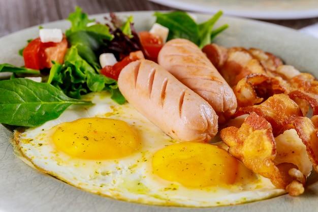 Repas pour le petit déjeuner œuf, bacon, salade et saucisse.