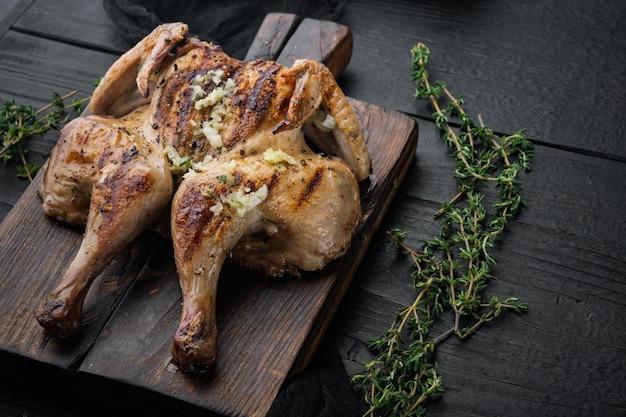 Repas de poussin spatchcock rôti, sur table en bois noir