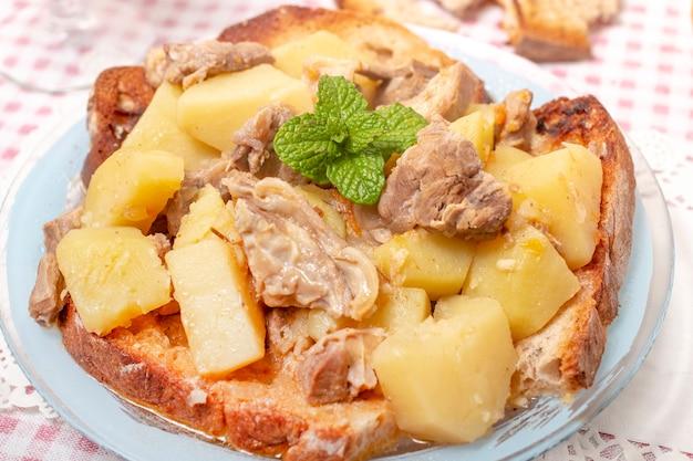 Repas typiquement portugais de ragoût d'agneau avec pommes de terre et pain grillé.