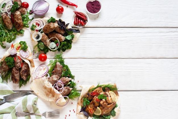 Repas de viande grillée sur table en bois blanc. assortiment sur assortiment de grillades chaudes, espace libre