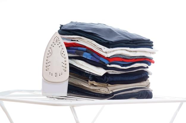 Repassage électronique et pile de vêtements à bord sur fond blanc isolé
