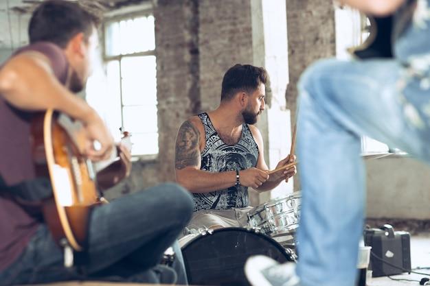 Répétition du joueur de guitare électrique du groupe de musique rock et du batteur derrière la batterie