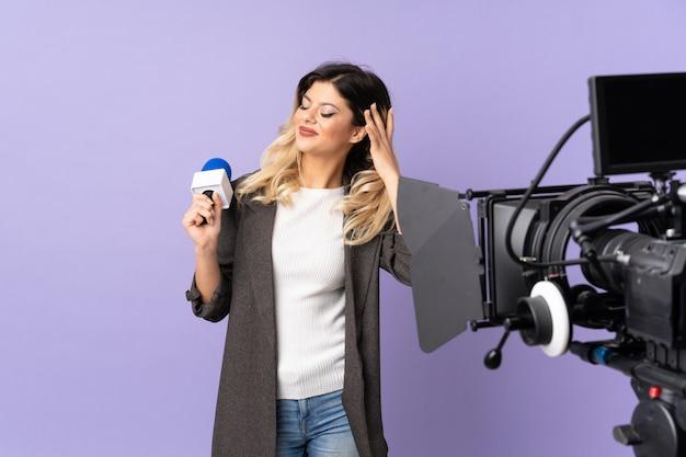 Reporter adolescent fille tenant un microphone et rapporter des nouvelles sur le mur violet en pensant à une idée