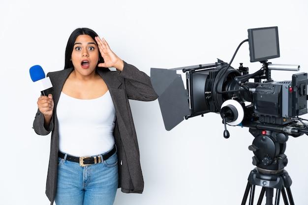 Reporter femme colombienne tenant un microphone et rapportant des nouvelles sur blanc avec expression surprise